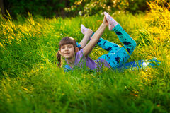 Beautiful girl doing yoga outdoors On green grass Royalty Free Stock Photo