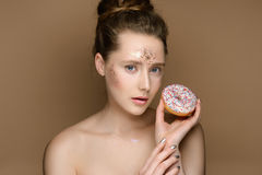 Beautiful girl with donut in hand and tinsel makeup. Portrait of young beautiful girl with donut in hand and updo on the gold background. Nude makeup with tinsel Royalty Free Stock Photos