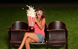 Beautiful girl down his popcorn order to expose you scared Royalty Free Stock Photography