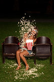 Beautiful girl down his popcorn order to expose you scared Royalty Free Stock Image