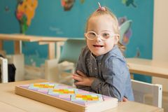 Beautiful girl with down syndrome engaged in class. Beautiful girl with down syndrome  engaged in class Royalty Free Stock Photo