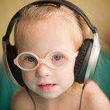 Beautiful girl with Down syndrome is listening to music on headphones Stock Images