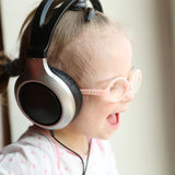 Beautiful girl with Down syndrome is  listening to music on headphones Royalty Free Stock Photos