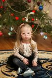 Beautiful girl with Down syndrome sits near a Christmas tree Royalty Free Stock Image