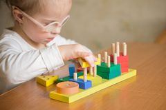 Beautiful girl with Down  syndrome sorts geometric shapes Stock Image