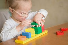 Beautiful girl with Down  syndrome sorts geometric shapes Stock Photography