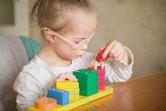 Beautiful girl with Down  syndrome sorts geometric shapes Royalty Free Stock Photos