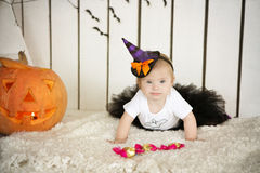 Beautiful girl with Down syndrome thoughtfully keeps finger in the mouth near the big pumpkin Royalty Free Stock Image