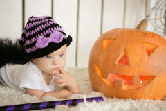 Beautiful girl with Down syndrome thoughtfully keeps finger in the mouth near the big pumpkin Royalty Free Stock Photos