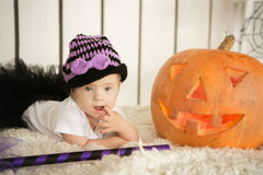 Beautiful girl with Down syndrome thoughtfully keeps finger in the mouth near the big pumpkin. Beautiful girl with Down syndrome thoughtfully keeps finger in the Stock Photography