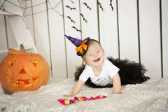 Beautiful girl with Down syndrome thoughtfully keeps finger in the mouth near the big pumpkin Stock Images