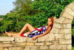 Beautiful girl draped in American flag. Royalty Free Stock Photo