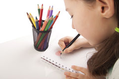 Beautiful girl is drawing with color pencils. Isolated in white Royalty Free Stock Image