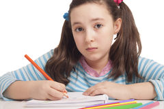Beautiful girl is drawing with color pencils. Isolated in white Royalty Free Stock Photo
