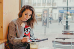 Beautiful girl drawing with pencil in cafe Stock Images