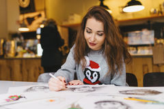 Beautiful girl drawing with pencil in cafe Stock Photos