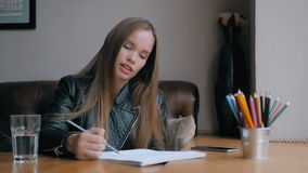 Beautiful girl drawing with pencil, cup of water and colorful pencils on wooden table, mock up, big window stock video