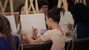 Beautiful girl draws flowers brush in art class stock footage