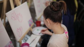 Beautiful girl draws flowers brush in art class stock video footage