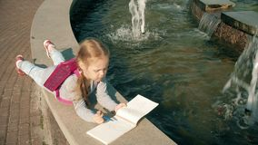 Beautiful girl draws in a notebook near the fountain stock video