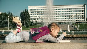 Beautiful girl draws in a notebook near the fountain. N 4k stock video footage