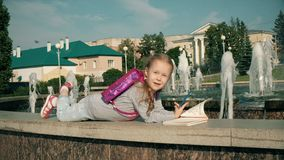 Beautiful girl draws in a notebook near the fountain stock video footage