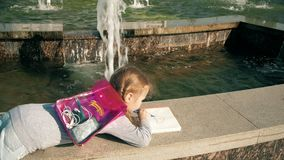Beautiful girl draws in a notebook near the fountain stock footage