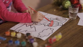 Beautiful girl draws a picture of a Christmas tree and a snowman. Little girl draws a Christmas picture. Child paints a snowman stock footage