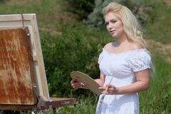 Beautiful girl draws a picture in the park using a palette with paints. Easel and canvas with a picture. stock images