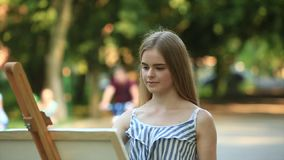 Beautiful girl draws a picture in the park using a palette with paints and a spatula. Easel and canvas with a picture.  stock video