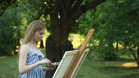 Beautiful girl draws a picture in the park using a palette with paints and a spatula. Easel and canvas with a picture.  stock footage