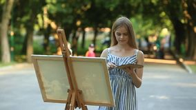 Beautiful girl draws a picture in the park using a palette with paints and a spatula. Easel and canvas with a picture. Summer is a stock video