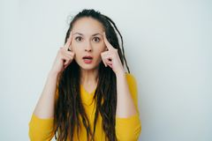 Beautiful girl with dreadlocks and in a yellow bright sweater is surprised looking at the camera and holding her hands at the stock photo