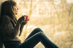 Beautiful girl dreaming with cup of coffee near window Royalty Free Stock Images