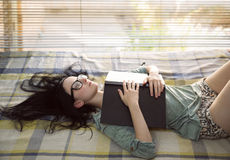 Beautiful girl dreaming with eyes open. Black-haired beautiful girl with tousled hair and eyeglasses lying down on her back on the bed holding book and dreaming royalty free stock photo