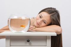 Beautiful girl dreams and sees a goldfish in an aquarium Stock Photography