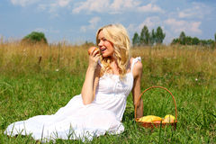 Beautiful girl in dress. The beautiful girl with an apple in the field stock images