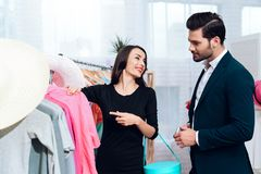 Beautiful girl in a dress and an attractive man in suit are shopping. They are in a light showroom. stock photo