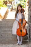 Beautiful girl in a dress with a cello stands on the steps