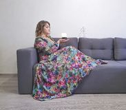 beautiful girl in dress, curly hair, sitting, elegant couch stock photography