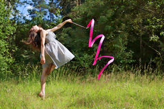 Beautiful girl in dress is engaged in rhythmic gymnastics Stock Photography