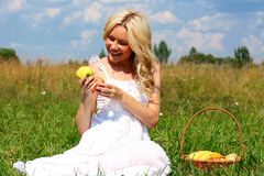 Beautiful girl in dress. Happy girl with blond hair and apples in their hands Royalty Free Stock Photo