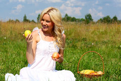 Beautiful girl in dress. Happy girl with blond hair and apples in their hands stock photography