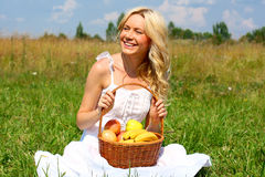 Beautiful girl in dress. Happy girl with blond hair and a basket of fruit Stock Images