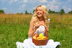 Beautiful girl in dress. Happy girl with blond hair and a basket of fruit royalty free stock photo