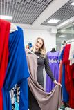 Beautiful girl with dress. Happy young woman choosing clothes in mall or clothing store. Sale, fashion, consumerism. Happy young woman choosing clothes in mall stock image