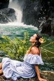 Girl sitting by the waterfall. Beautiful girl in a dress and a Hibiscus flower in her hair sitting by the waterfall, the concept of leisure and travel Royalty Free Stock Photos