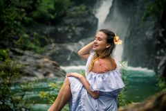 Girl sitting by the waterfall. Beautiful girl in a dress and a Hibiscus flower in her hair sitting by the waterfall, the concept of leisure and travel Royalty Free Stock Image