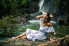 Girl sitting by the waterfall. Beautiful girl in a dress and a Hibiscus flower in her hair sitting by the waterfall, the concept of leisure and travel Stock Images