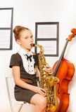 Beautiful girl in dress holding alto saxophone Royalty Free Stock Photography
